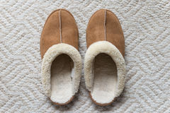 A pair of winter slipper. A pair of brown suede winter slipper on the light grayish brown color area rug Royalty Free Stock Image