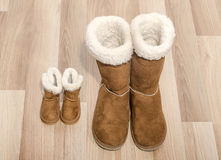 Pair of winter woman boots and similar pair of kid boots. Matching big and small boots stock photos