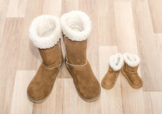 Pair of winter woman boots and similar pair of kid boots. Stock Photo
