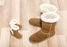 Pair of winter woman boots and similar pair of kid boots. Matching big and small boots royalty free stock image