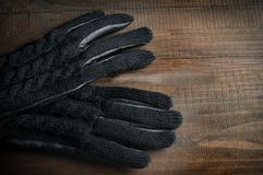 Pair of woman's black leather gloves on wooden table Royalty Free Stock Photo
