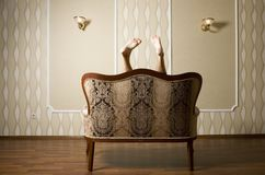 Pair of a Woman's Feet over  Classic King Sofa Royalty Free Stock Images