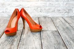 Pair of woman shoes on a wooden floor and free space. Royalty Free Stock Image