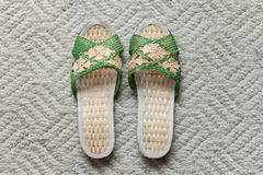A pair of woman slipper. A pair of light brown and green hand weaved woman slipper on a light grayish brown area rug Stock Photography