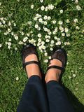 Pair of womans feet in black leather shoes on grass Stock Photo