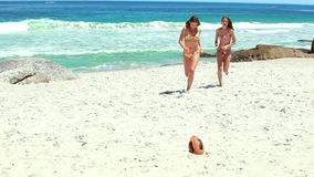 A pair of women in bikinis running towards a rugby ball. At the beach stock footage