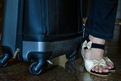 Pair of women black and white colored heels travel bag in background royalty free stock photo