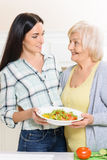 Pair of women holding salad in kitchen Royalty Free Stock Photo