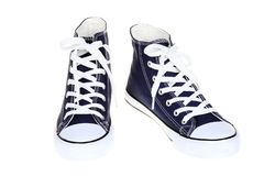 Pair of women`s high top lace up dark navy blue sneakers isolated on white background Royalty Free Stock Photos