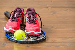 Pair of women`s sneakers on a tennis racket Royalty Free Stock Photography