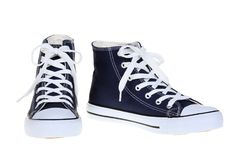 Pair of womens high top lace up dark navy blue sneakers isolated on white background Stock Images