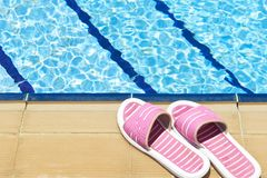 Beach Shoes. A pair of womens plastic sandals by side of swimming pool royalty free stock photo