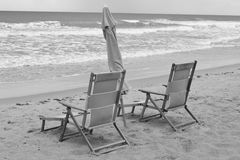 Pair of wooden beach chairs and umbrella Stock Photos