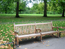 Pair of wooden benchs. Wooden benchs in a park in autumn Royalty Free Stock Image