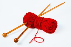 Pair of wooden knitting needles and red wool - white background royalty free stock photography