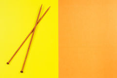 Pair of wooden knitting needles on yellow and orange background Stock Photography