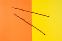 Pair of wooden knitting needles on yellow and orange background Royalty Free Stock Photo