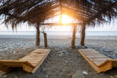 Pair of wooden sunbeds under a canopy of cane roof on the beach at sunset.  stock photo