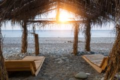 Pair of wooden sunbeds under a canopy of cane roof on the beach at sunset.  stock image