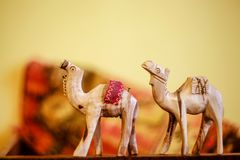 A pair of wooden toy camel. On a yellow background stock photography