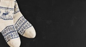 Pair of wool socks with pattern deer on black. Background. Warm winter stockings with traditional christmas ornament, copy space Royalty Free Stock Images