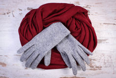 Pair of woolen gloves and shawl for woman on old wooden background Royalty Free Stock Photo