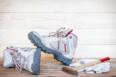 Pair of work boots with gloves and hammer on wooden background Royalty Free Stock Photo