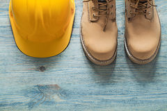 Pair of working boots building helmet on wooden board constructi Stock Images