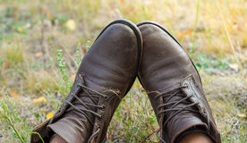 A pair of worn brown leather shoes over the countryside background Royalty Free Stock Photos