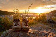 A Pair of Worn Hiking Boots. On mountain with view towards the sun and city center at cloudy orange sunset stock photo