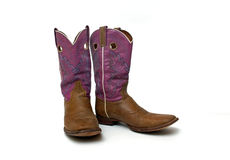 Pair of worn women's cowboy boots. A brown and purple pair of old cowboy boots for women royalty free stock photos