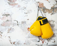 Pair of yellow boxing gloves hanging Stock Photography