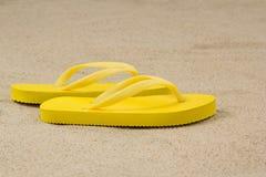 Pair of yellow flip flops on beach Stock Photography