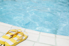 Pair of yellow flip flops by the pool side Stock Images