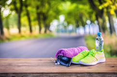 Pair of yellow green sport shoes towel water smart pone and headphones on wooden board. In the background forest or park trail. Royalty Free Stock Images