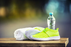 Pair of yellow green sport shoes towel water smart pone and headphones on wooden board. In the background forest or park trail. Accessories for running sport Royalty Free Stock Photo
