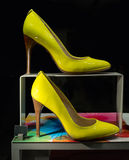 Yellow Women's Shoes on a Display. A pair of yellow high heel women's shoes on a colourful display with black background. Clipping path around the shoes included royalty free stock photos