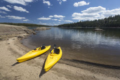 Pair of Yellow Kayaks on Beautiful Mountain Lake Shore. Royalty Free Stock Images