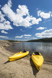 Pair of Yellow Kayaks on Beautiful Mountain Lake Shore. Royalty Free Stock Image