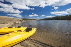 Pair of Yellow Kayaks on Beautiful Mountain Lake Shore. Royalty Free Stock Photography