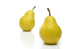 A pair of yellow pears. With drops, one on front and one  backwards (out of focus) over a white background. Look for more fruits and vegetables at my gallery Stock Photos