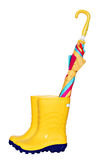 Pair of yellow rubber boots with colorful umbrella Royalty Free Stock Image