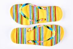 Pair of yellow striped flip flops. Female beautiful shoes for sea vacation. Comfortable footwear for summer rest royalty free stock images