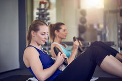 Pair of young adult women doing abdominal muscle exercises stock photography