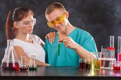 A pair of chemists are examining a flask with a green liquid. The concept of science. On a dark background. stock photography