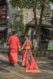 A pair of young couples who are facing each other wearing Chinese traditional red wedding dresses and smiling at each other in the. A pair of young couples who stock images