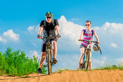 Pair of young cyclists on the hill against the sky Stock Photo