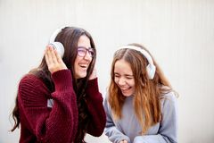 A couple of teenage girls have fun with their headphones royalty free stock photos