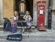 A pair of young musicians perform in the Old Town of Warsaw in Poland. Royalty Free Stock Images