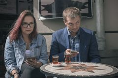 Pair of young people a man and a girl are sitting at a table of royalty free stock images